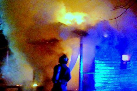 A fire fighter sprays a smoking fire with a fire hose at night.