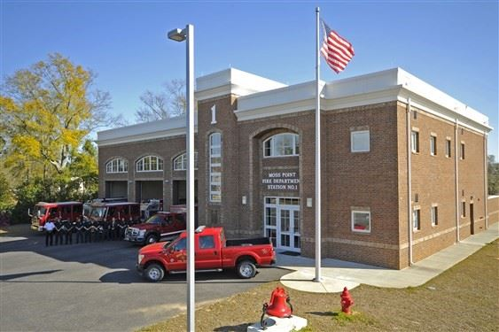 The front of the Central Fire Station #1 with a truck parked in front of the doors and fire trucks o