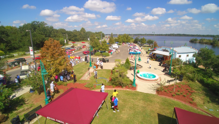 Aerial image of the Riverfront Park with outbuildings, tents, and visitors