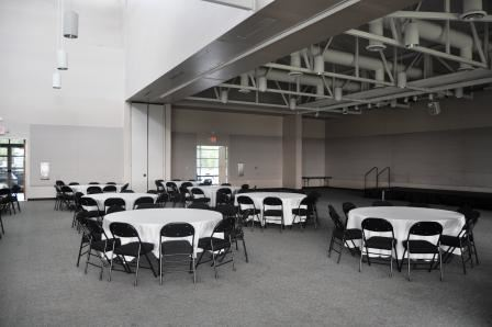 A room with round tables and chairs around them.