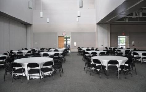 A room full of round tables with chairs around them.