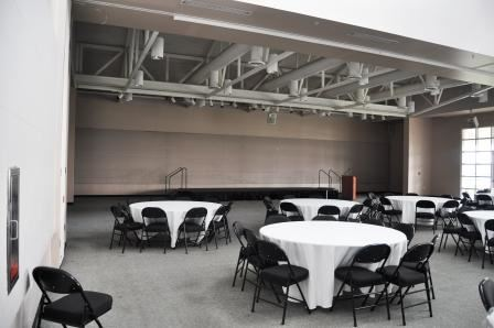 Round tables with chairs around them in an empty room.