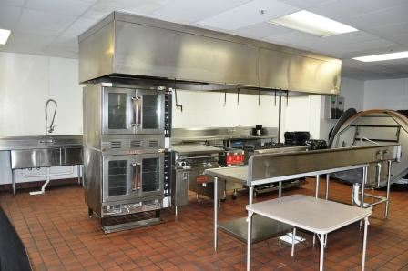 The kitchen in Pelican landing with two ovens and stainless steel counters.