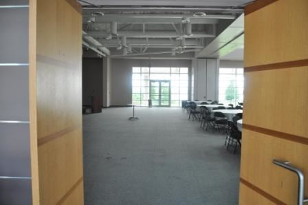 An empty room in the Pelican Landing Event and Conference center with tables and chairs set up and a full wall of windows in the back.